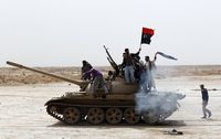 670829_rebels-wave-a-kingdom-of-libya-flag-as-they-ride-on-top-of-a-tank-on-the-outskirts-of-ajdabiyah-on-the-road-leading-to-brega